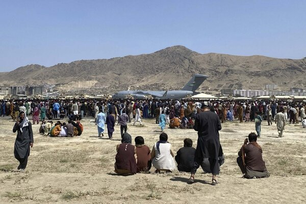 In this photo, taken on Aug. 16, 2021, hundreds of people gather near a U.S. Air Force C-17 transport plane along the perimeter at the international airport in Kabul, Afghanistan.