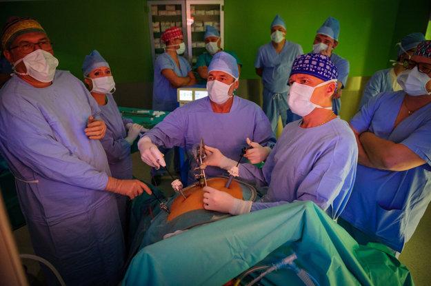 Priebeh operácie sledujú chirurgovia na monitore.