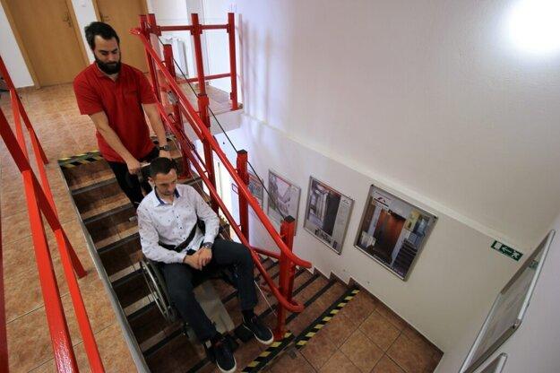 Pásový schodolez pri preprave invalidného vozíka po schodisku